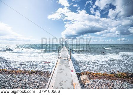Small Bridge To The Cold Sea With Waves Coming In On The Pebble Beach