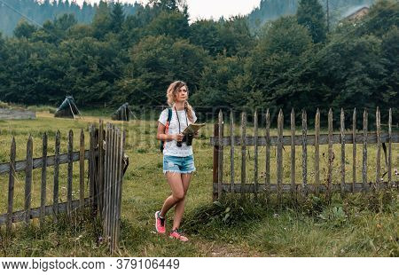 Girl With A Backpack And Binoculars Is Searching The Route On The Map Holding It In Her Hands. In Th