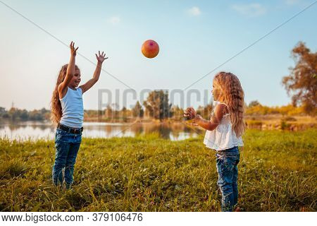 Little Girl Playing With Ball With Her Sister In Summer Park. Kids Having Fun Outdoors. Games For Ch