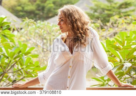 Young beautiful casual dressed girl wearing white shirt in tropical garden on a sunny day