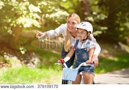 Mom Teaching Daughter To Ride A Bicycle Encouraging Her And Showing Direction Spending Time Together