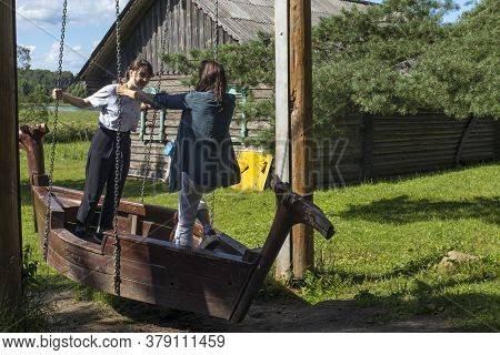 Uchemskiy Museum Of The Cassian Desert And The Fate Of Russian Village. Girls Tourists Swing On A Wo