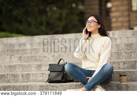 Communication And Education Concept. Cheerful Asian Teen In Specs Making Phone Call, Sitting On Step