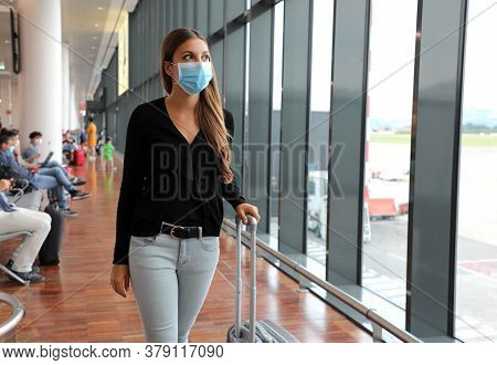 Young Business Woman With Surgical Mask And Travel Trolley Luggage Walking Inside The Airport. Femal