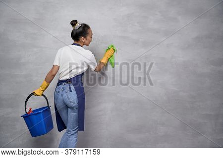 Full Disinfection. Back View Of Housewife Or Maid Woman Uniform And Yellow Rubber Gloves Holding Buc
