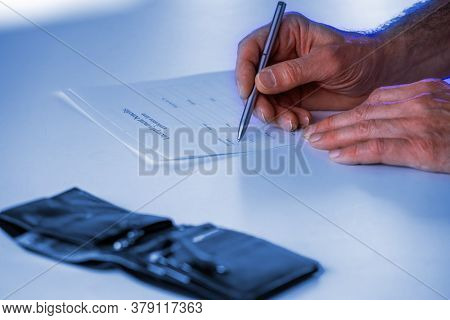 Man signs a utilities invoice with a ballpoint pen in the office