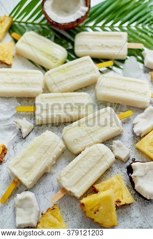 Summer popsicles on stick. Pinacolada flavour. Made with pineapple, cocount milk and rum. Vegan snack. Decorated with fresh fruit. Top view. Flat lay.