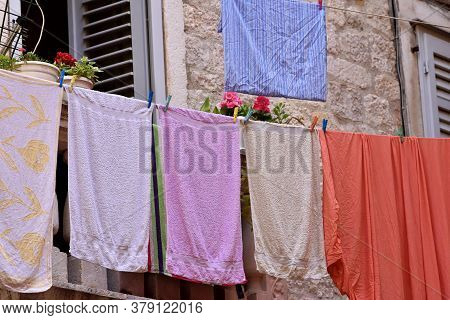 Multi-colored Laundry Dries After Washing Outside The Window On The Street/ Typical Mediterranean Sc