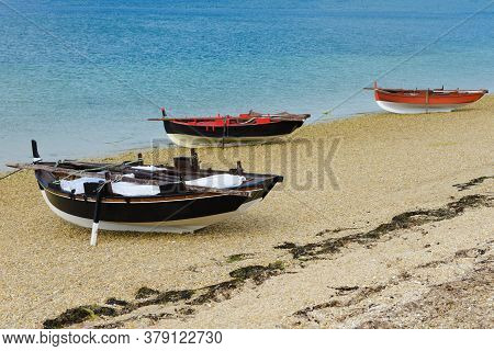 Black And Red Wooden Fishing Boats Dry On The Seashore