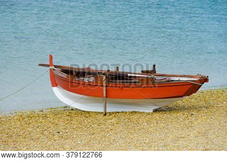 Red Wooden Fishing Boat Dries Up On The Seashore