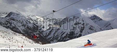 Chair-lift, Snowy Ski Track Prepared By Snowcat, Skiers On Ski Resort. High Winter Mountains And Blu