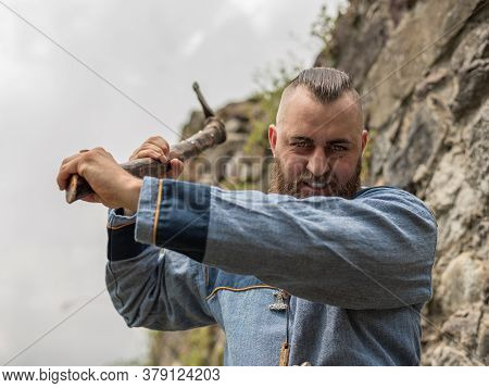 A Man In Medieval Clothes Wields An Ax In The Ruins Of An Ancient Castle