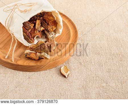 Dried Mushrooms In A Canvas Bag Scattered On A Wooden Tray On A Background Of Burlap. Organic, Eco-f