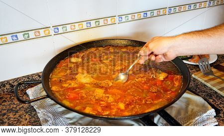 View Of The Cooking Process Of A Valencian Paella, Man Is Hand Removing The Ingredients. Gastronomy