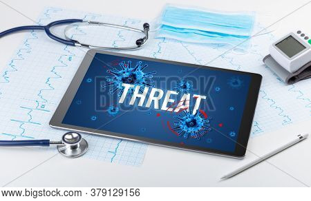 Tablet pc and doctor tools on white surface with THREAT inscription, pandemic concept