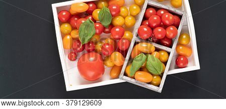 Top view of cherry tomatoes in small wooden crate