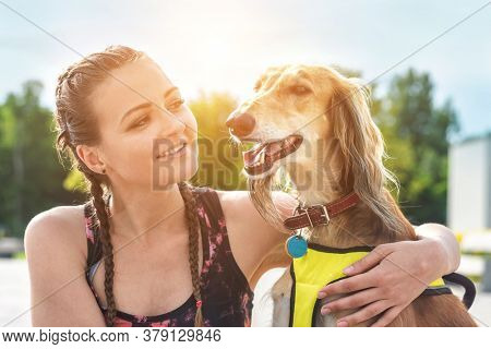 Woman runner and dog on city street under sunrise sky in morning time. Outdoor walking. Athletic young girl with his dog are running in town.