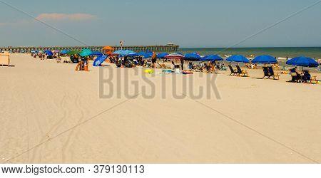 Beachgoers Under Blue Umbrellas In Myrtle Beach Sc