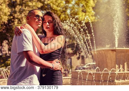 Loving Young Couple At The Park With A Fountain