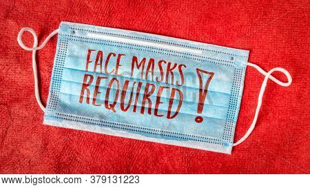 face masks required - text on a disposable mask against red textured paper, business sign during the coronavirus covid-19 pandemic and social distancing