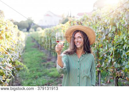 Woman With Wineglass Of Pink Wine In Vineyard At Sunset. Wine Tasting In Winery. Traveler Enjoying L