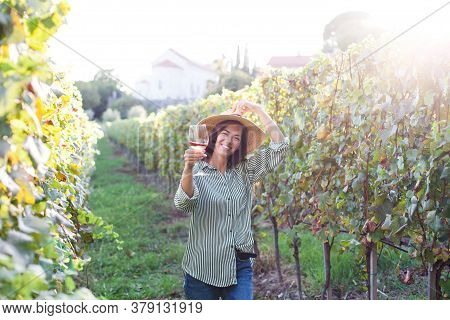 Wine Tasting In Winery. Woman Fatmer Holds Wineglass With Pink Wine In Vineyard. Happy Traveler In S