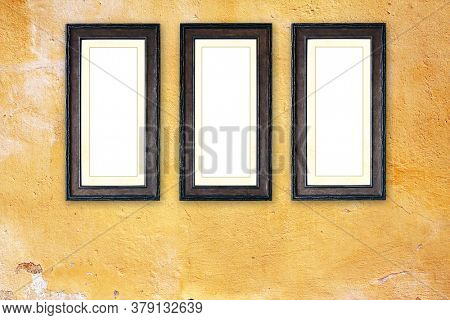 Three vintage wooden empty picture frames on old stucco wall. Retro blank frame on room wall. Mock up template. Copy space for text