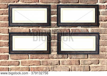 Four vintage wooden empty picture frames on old brick wall. Retro blank frame on room wall. Mock up template. Copy space for text