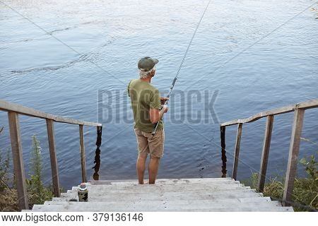 Backwards View Of Man Catching Fish While Posing On Wooden Stairs Leading To Lake, Male Wearing Casu