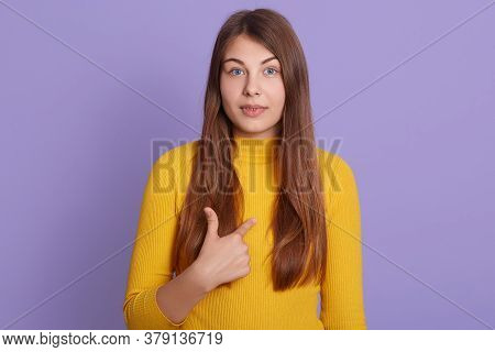 Studio Shot Of Astonished Woman With Long Hair Points At Herself, Wears Yellow Jumper, Has Surprised