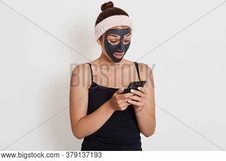 Young Teenage Girl With Black Face Mask On Her Face Using Her Smart Phone, Looking At Device Screen