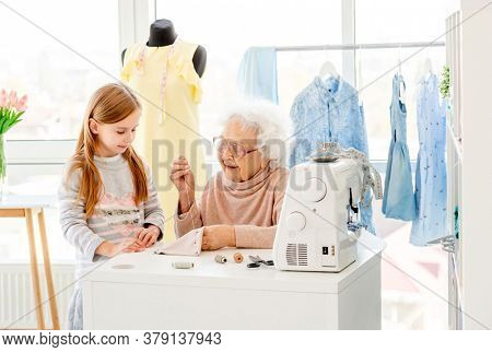 Granny sewing with granddaughter in workshop