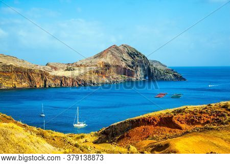 Madeira is island in the Atlantic. The west coast of the island of Madeira - the bay between the rocks with yachts and boats. The blinding midday sun.