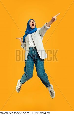 Jumping High Emotional. Young Muslim Woman In Casual On Yellow Studio Background. Stylish, Trendy. B