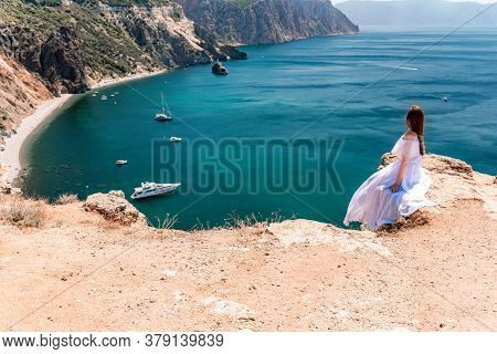 A Woman In A White Flying Dress Is Seen Behind, Fluttering In The Wind. Sitting On The Background Of