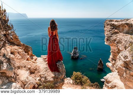 From Behind, A Woman Is Seen In A Red Flying Dress Fluttering In The Wind Against The Background Of