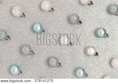Repetitive Pattern Made Of Christmas Baubles On A Silver Textured Background. Glowing New Year Compo