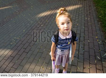 A Tired Elementary School Girl Looks Sadly At The Camera. Primary And Pre-school Education, Learning