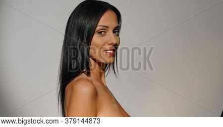 Side view of natural woman smiling to camera. Body care and feminine.