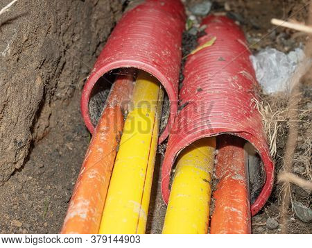 Yellow And Orange Plastic Cores Of Optic Data Fibers Go Through Red Ribbed Hdpe Tube. Internet Provi