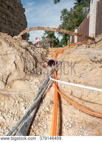 Orange Fiber Optic Cables On A Construction Site. Building Of Lines Of Metallic And Fiber Optic Cabl