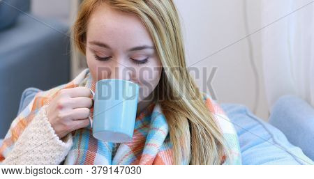 Portrait of a woman relaxing at home with a cup of tea.