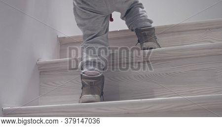 Baby climbing thewooden stairs at home
