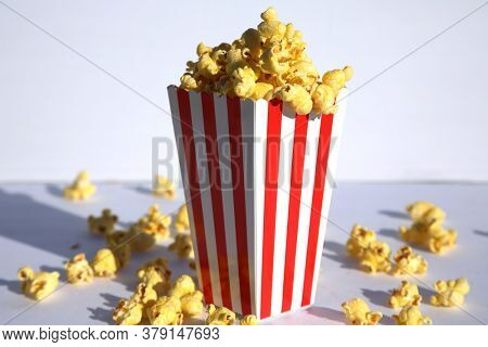 Popcorn. Popcorn in a White and Red Striped Container. On a Gray Background. Popcorn Text. Popcorn is enjoyed world wide by happy people and animals alike. Room for text. Clipping Path.