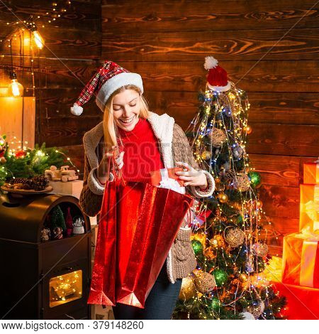 Happy Smiling Woman In Santas Hat Hold Red Pocket With Christmas Presents Gifts. Christmas Gifts. Jo