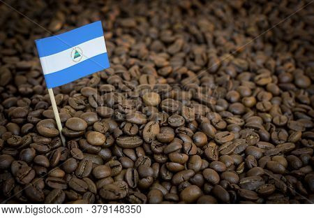 Nicaragua Flag Sticking In Roasted Coffee Beans. The Concept Of Export And Import Of Coffee
