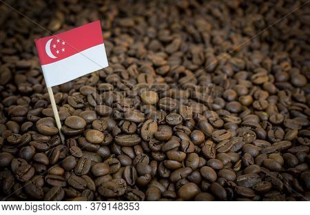 Singapore Flag Sticking In Roasted Coffee Beans. The Concept Of Export And Import Of Coffee