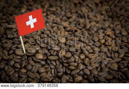Switzerland Flag Sticking In Roasted Coffee Beans. The Concept Of Export And Import Of Coffee