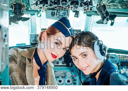 Portrait Of Two Smiling Women Pilots. Beautiful Smiling Young Woman Pilot Sitting In Cabin Of Modern