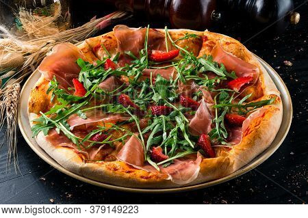 Pizza With Prosciutto Parma Ham, Arugula Salad Rocket And Strawberries On Wooden Background Italian